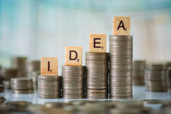 Stack of Coins with Wooden Letters Stock Image