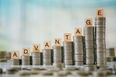 Stack of Coins with Wooden Letters Royalty Free Stock Images