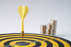 Stack of coins. Yellow dart hit in the center of a target with stack of coins behind on white background with copy space. A idea about money / currency Royalty Free Stock Photography
