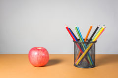 A stack of color pencils and apple. Stock Image