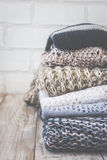 Stack of colored cozy knitted sweaters on a wooden rustic table, knitting bamboo needles. Toned retro. Stock Photo