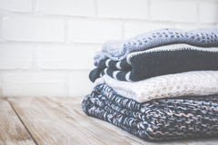 Stack of colored cozy knitted sweaters on a wooden rustic table, knitting bamboo needles. Toned retro. Stock Photography