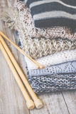Stack of colored cozy knitted sweaters on a wooden rustic table, knitting bamboo needles. Toned retro. Royalty Free Stock Images