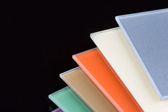 A stack of colored glass on a black background. Design, glass sheets Stock Photos