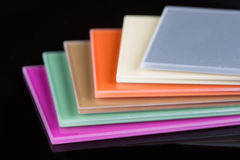 A stack of colored glass on a black background. Design, glass sheets Royalty Free Stock Images