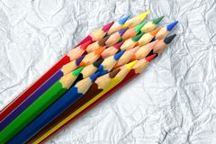 A stack of colored pencils on crumpled paper backg Stock Images