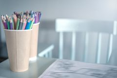 Stack of colored pencils in a glass on children`s table, next to a high chair ,left, A cozy place to draw for kids. royalty free stock image