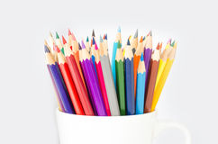 Stack of colored pencils in a glass on white background. Stack of colored pencils in a glass on white background Stock Images
