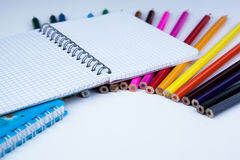 A stack of colored pencils with notebook. A stack of colored pencils notebook close-up Stock Photo