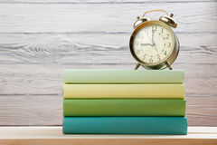 Stack of colorful books and alarm clock on wooden table. Back to school. Copy space.  Royalty Free Stock Image