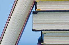 A stack of colorful books on a blue background Stock Image
