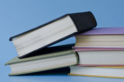 A stack of colorful books on a blue background Royalty Free Stock Image