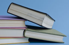 A stack of colorful books on a blue background Stock Photos