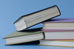 A stack of colorful books on a blue background Stock Photography