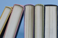 A stack of colorful books on a blue background Royalty Free Stock Images