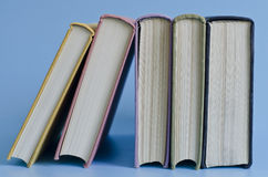 A stack of colorful books on a blue background Royalty Free Stock Photos