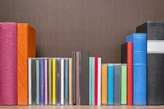 Stack of colorful books, cd and cassettes in the book self Stock Photo