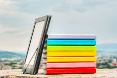 Stack of colorful books with electronic book reader Stock Images