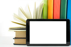 Stack of colorful books and electronic book reader. Electronic library concept. Back to school. Copy space Stock Photos