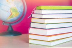 Stack of colorful books and globe, bright colorful pink background, free copy space. Books on table, no labels, blank spine. Back