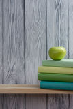 Stack of colorful books and green apple on wooden table. Back to school. Copy space stock images