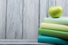 Stack of colorful books and green apple on wooden table. Back to school. Copy space.  Royalty Free Stock Image
