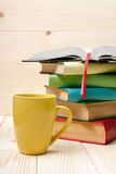 Stack of colorful books, open book and cup on wooden table royalty free stock image