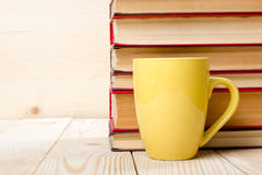 Stack of colorful books, open book and cup on wooden table Stock Photos