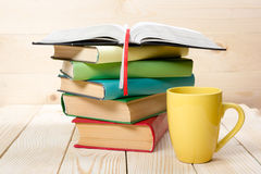 Stack of colorful books, open book and cup on wooden table. Back to school. Copy space.