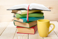 Stack of colorful books, open book and cup on wooden table. Back to school. Copy space stock photography
