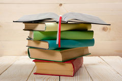 Stack of colorful books, open book on wooden table. Back to school. Copy space Stock Photography