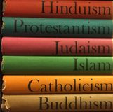 Stack of colorful books on religion. A colorful collection of stacked regions books on Hinduism, Protestantism, Judaism, Islam, Catholicism, Buddhism stock photos