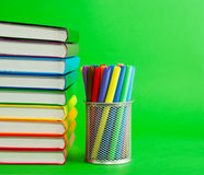 Stack of colorful books and socket with felt pens Stock Photography