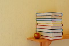 Stack of colorful books. Stack of colorful children books and red apple on bookshelf on yellow wall background with copy space for text. Reading learning stock images