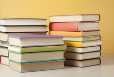 Stack of colorful books on the wooden table. Education background. Back to school. Stack of books on wooden table on yellow wall background. Back to school Royalty Free Stock Photo