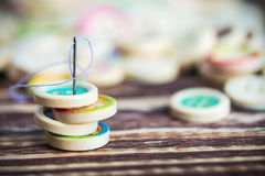 Stack of colorful buttons with sewing needle. On a wooden table. Focus on the needle's eye, very shallow depth of field Stock Photography