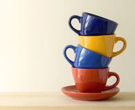 Stack of colorful coffee cups on table Royalty Free Stock Images