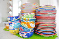 Stack of colorful hand painted ceramic bowls and plates Stock Photo