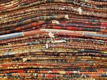 Stack of colorful handmade antique Oriental style rugs and carpe Royalty Free Stock Photos