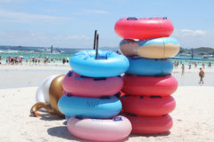 Stack of colorful inflatable swimming rings on the beach in sunny day. Royalty Free Stock Photography
