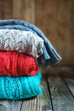 Stack of colorful  knitted sweaters on wooden Stock Photography