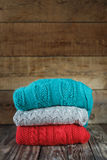 Stack of colorful knitted sweaters on wooden Stock Image