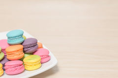 Stack of colorful macaroons cookies in dish on wood background w Stock Photos