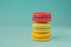 Stack of colorful macaroons stacked up like a tower in turquose pastel  background. Stock Photography