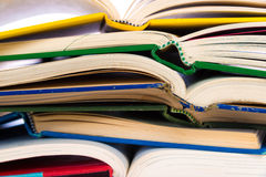 A stack of colorful, open books on a white background Stock Photos
