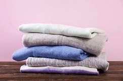 Composition with folded clothes, unisex for both man and woman, different color & material. Pile of laundry, dry clean clothing. Stack of colorful perfectly stock image
