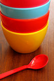 Stack of colorful plastic bowl with blue spoon Royalty Free Stock Photo
