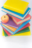 Stack of colorful real books, apple on white background, partial view. Back to school, Copy Space. Education . Stock Images