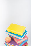 Stack of colorful real books, apple on white background, partial view. Back to school, Copy Space. Education . Stock Photo