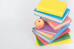 Stack of colorful real books, apple on white background, partial view. Back to school, Copy Space. Education . Stock Photos